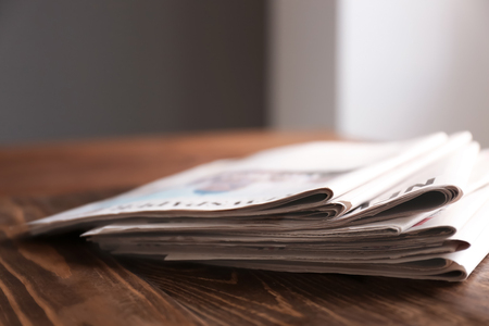 Pile of newspapers on wooden table Stock Photo