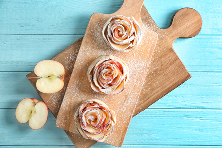Tasty rose shaped apple pastry on wooden boards