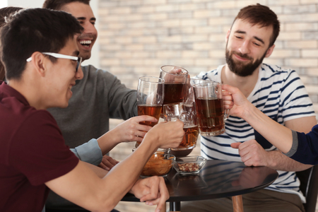 Group of friends clinking glasses with beer in bar
