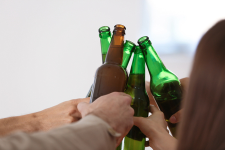 Group of friends clinking bottles with beer in bar