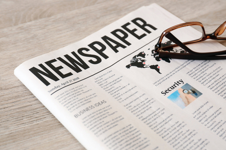 Newspaper with glasses on wooden background Archivio Fotografico