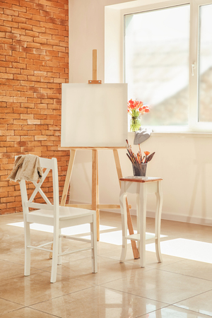 Easel with canvas and artist's supplies in workshop