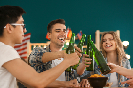 Group of cheerful friends drinking beer in bar Banco de Imagens