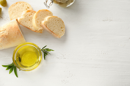 Bread and olive oil on wooden table Imagens