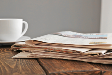 Pile of newspapers with cup of tea on wooden table