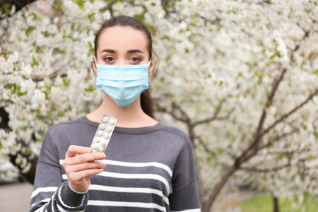 Young woman in protective mask holding pills near blooming tree. Allergy concept