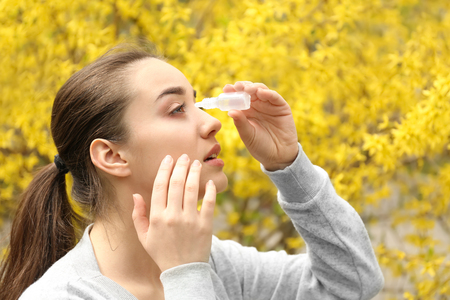 Young woman using eye drops near blooming tree. Allergy concept Stock Photo