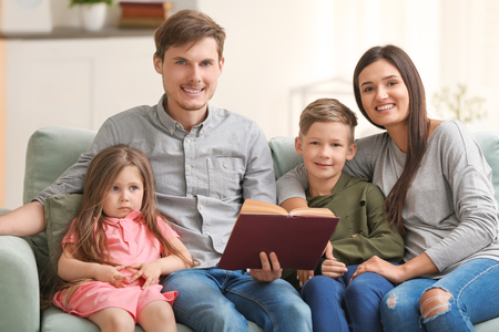 Happy family reading book together at home Stock Photo