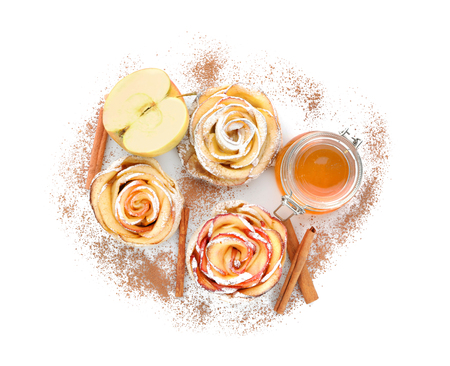 Tasty rose shaped apple pastry with cinnamon and honey on white background