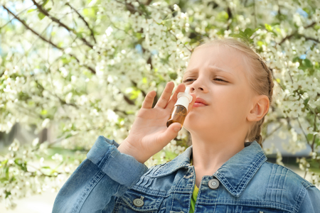 Little girl using nasal drops near blooming tree. Allergy concept