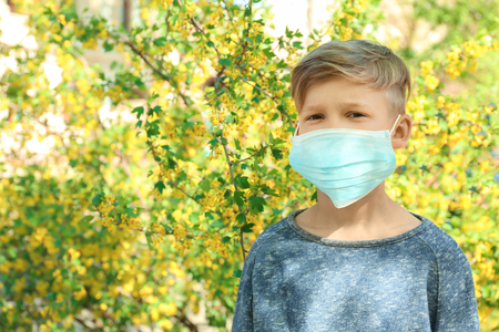 Little boy in protective mask near blooming tree. Allergy concept