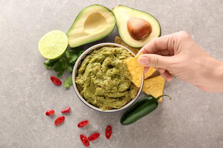 Mujer comiendo delicioso guacamole con nachos, primer plano