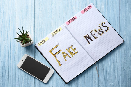 Notebook with words FAKE NEWS and mobile phone on wooden background