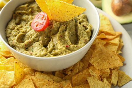 Bowl with delicious guacamole and nachos on plate, closeup