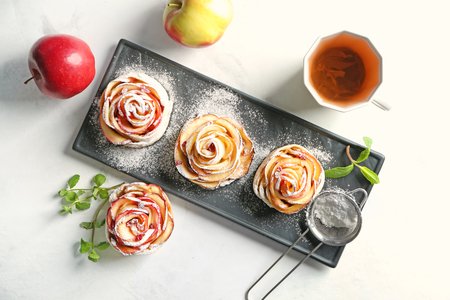Plate with tasty rose shaped apple pastry on table