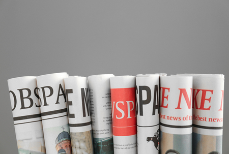 Folded newspapers on grey background