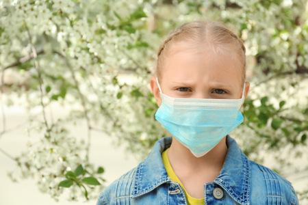 Little girl in protective mask near blooming tree. Allergy concept Stock Photo
