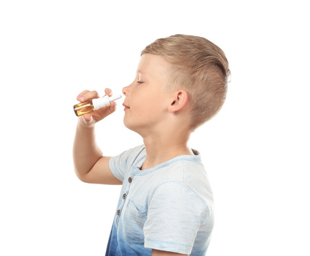 Little boy using nasal drops on white background. Allergy concept