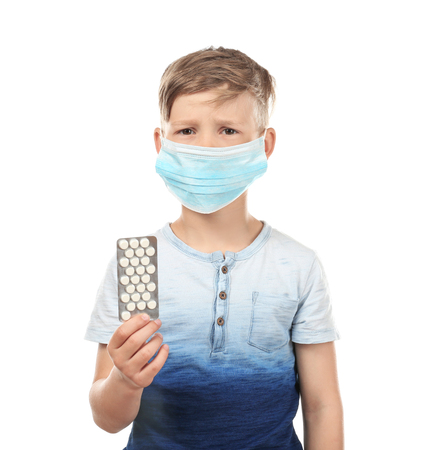 Little boy in protective mask holding pills on white background. Allergy concept