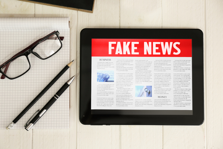 Fake news displayed on tablet computer screen on wooden background