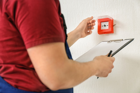 Werknemer met klembord in de buurt van moderne brandmelder op muur
