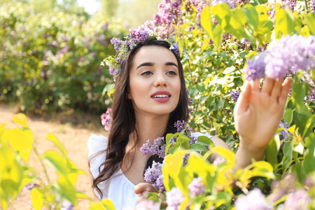 Beautiful young woman wearing flower wreath near blossoming shrub on sunny spring day