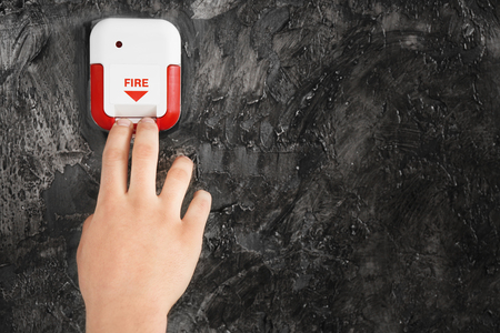 Young man using fire alarm system indoors