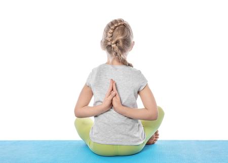 Niña practicando yoga sobre fondo blanco.