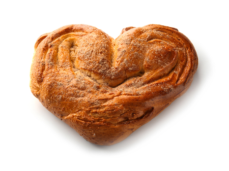 Sweet heart-shaped cinnamon bun on white background