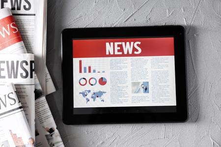 Tablet-Computer mit Nachrichten auf dem Bildschirm auf strukturiertem Hintergrund Standard-Bild