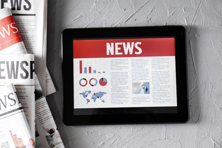 Tablet computer with news on screen on textured background Фото со стока