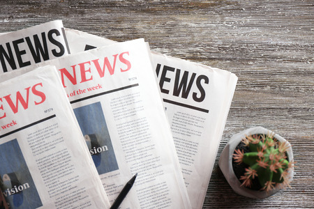 Morning newspapers on wooden background Imagens