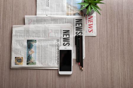 Composizione con giornali del mattino e telefono su fondo in legno Archivio Fotografico