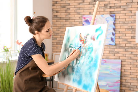 Künstlerin malt Bild in Werkstatt