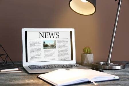 Lugar de trabajo con laptop y noticias en pantalla. Foto de archivo