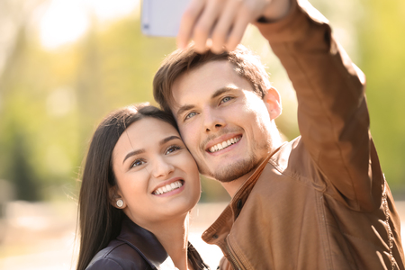 Young lovely couple taking selfie outdoors