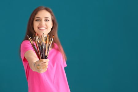 Beautiful female artist with set of brushes on color background