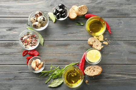 Frame made of olive oil and different products on wooden background Imagens