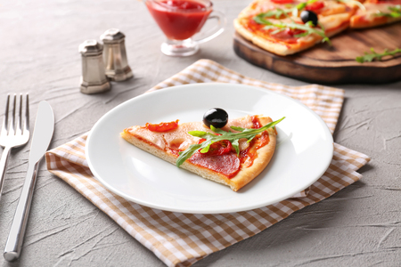 Plate with piece of tasty pizza on table