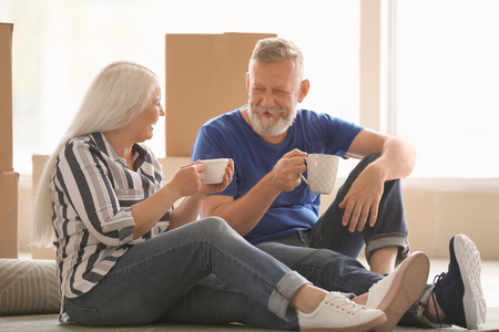Mature couple with belongings sitting on carpet and drinking tea indoors. Moving into new house Archivio Fotografico