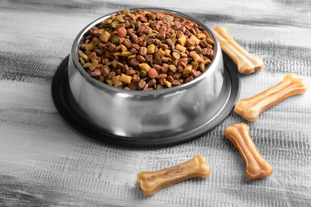Bowl with pet food on wooden background