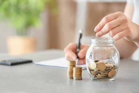 Frau, die Münzen in Glas auf Tisch setzt. Sparkonzept