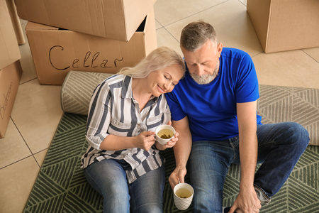 Mature couple with belongings sitting on carpet and drinking tea indoors. Moving into new house Stock Photo