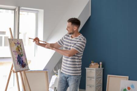 Male artist painting in workshop Imagens