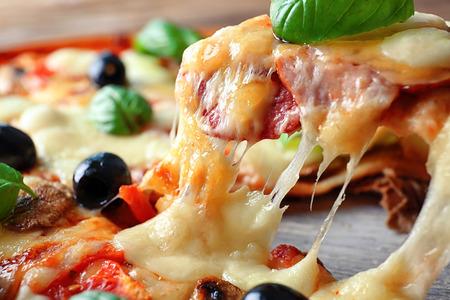 Slice of tasty Italian pizza on shovel, closeup