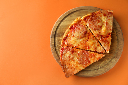 Wooden board with tasty pepperoni pizza on color background Stock Photo