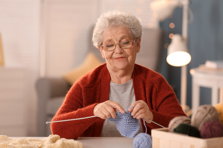 Senior woman knitting warm sock at table