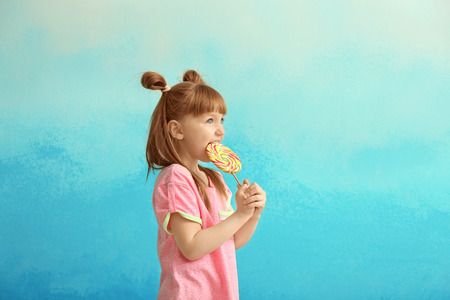 Cute little girl with lollipop on color background
