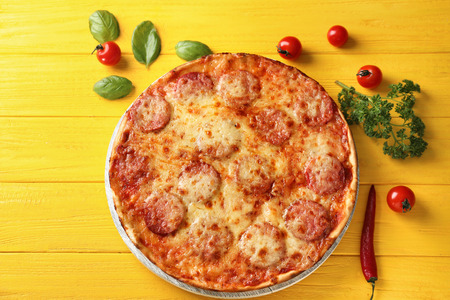 Tasty pepperoni pizza, tomatoes and herbs on color wooden background