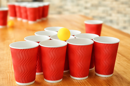 Cups and ball for beer pong on wooden table Foto de archivo